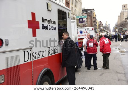 NEW YORK CITY - MARCH 27 2015: one day after a fire & explosion in Manhattan's East Village, 2 people remain missing as workers clear the wreckage of three destroyed brownstones.American Red Cross van - stock photo
