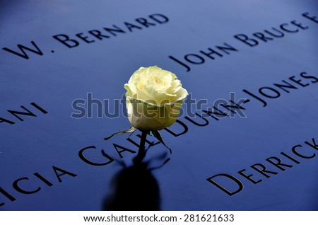 New York City - May 23, 2015:  A single white rose left in tribute amongst the inscribed victims names surrounding the 9/11 Memorial south tower footprint - stock photo