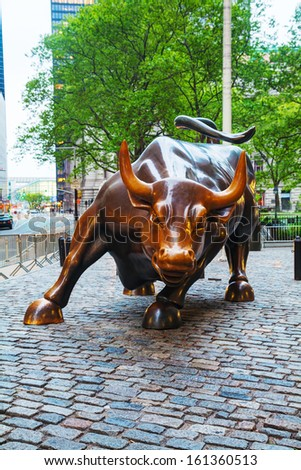 NEW YORK CITY - MAY 12: Charging Bull sculpture on May 12, 2013 in New York City. The sculpture is a popular tourist destination which draws thousands of people a day - stock photo