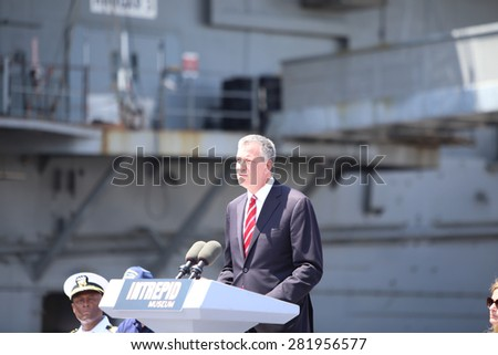 NEW YORK CITY - 25 MAY 2015: Mayor Bill de Blasio & Gen John Kelly presided over Memorial Day observances on Pier 86 by the USS Intrepid. Mayor de Blasio speaks on pier 86 with Intrepid background - stock photo