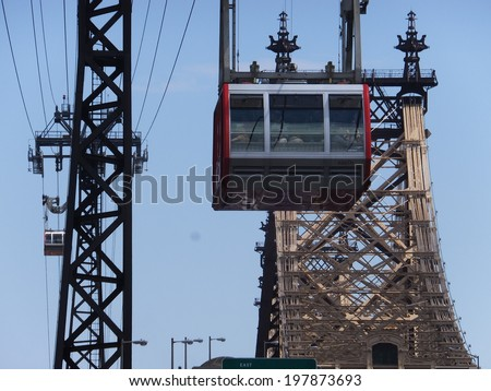 NEW YORK CITY - MAY 3: Roosevelt Island cable tram car that connects Roosevelt Island to Manhattan in New York, as seen on May 3, 2014.  The Queensboro bridge is also visible here. - stock photo