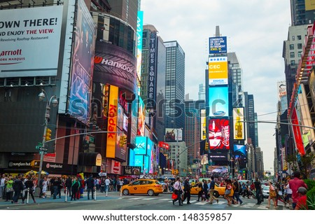 NEW YORK CITY - MAY 11: Times Square with tourists on May 11, 2013. It's the brightly illuminated hub of the Broadway Theater District, one of the world's busiest pedestrian intersections. - stock photo