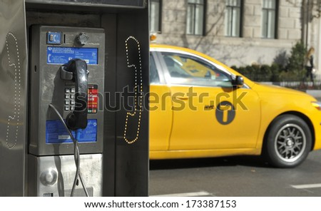 NEW YORK CITY, NEW YORK, USA - NOVEMBER 15, 2012: Old fashioned pay phone on a New York City street with a taxi passing by.November 15, 2012,New York - stock photo