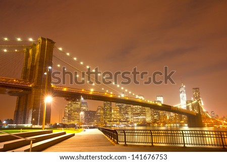 New York City night panorama with Brooklyn Bridge and illuminated downtown Manhattan business and residential buildings - stock photo