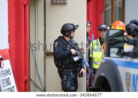 NEW YORK CITY - NOVEMBER 22 2015: Emergency response personnel staged an active shooter exercise in Manhattan's Lower East Side. Counter terrorism officer in tactical gear with fake assault rifle - stock photo