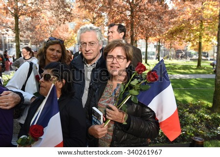 NEW YORK CITY - NOVEMBER 16 2015: Several hundred gathered at the 911 Memorial at Ground Zero to lay flowers at the base of the Survivor Tree in memory of the victims of the Paris terror attack - stock photo