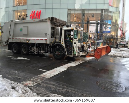 New York City, NY - January 26, 2016: New York City sanitation truck with a snow plow completes snow removal cleanup after Blizzard Jonas drops over two feet of snow in the tri-state area.  - stock photo