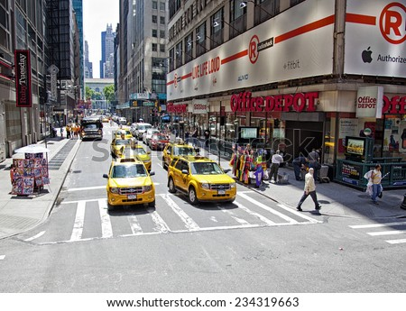 New York City, NY - June 28, 2014:  Intersection in Times Square with taxi cabs, pedestrians and store fronts in New York City, NY on June 28, 2014. - stock photo