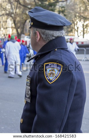 NEW YORK CITY, NY - NOVEMBER 28 : City of New York Policeman overlooking parade at W 59th ST during the Macy's 87th Annual Thanksgiving Day Parade on November 28, 2013 in New York City, New York.  - stock photo