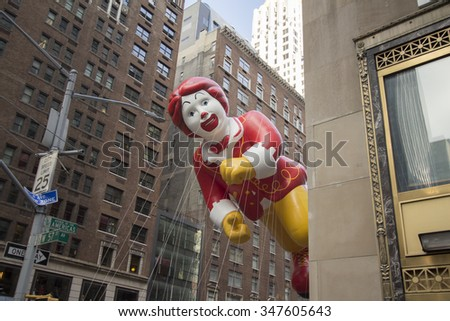NEW YORK CITY, NY - NOVEMBER 26:Ronald McDonald balloon flying between tall buildings in city street during the 89th Annual Macy's Thanksgiving Day Parade on November 26, 2015 in New York City. - stock photo