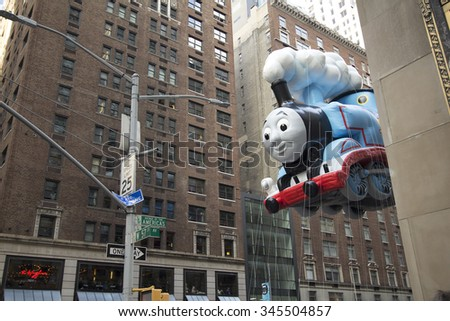 NEW YORK CITY, NY - NOVEMBER 26 : Thomas the Train float between buildings on 6th avenue during the Macy's 89th Annual Thanksgiving Day Parade on November 26, 2015 in New York City, New York.  - stock photo