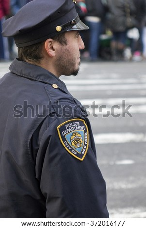 NEW YORK CITY, NY - NOVEMBER 26 -Young NYC Police Officer standing guard at Macy's 89th Annual Thanksgiving day parade to start on November 26, 2015 in New York City, New York. - stock photo