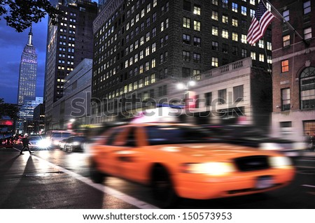 NEW YORK CITY - OCT 15 2009:New york taxi cab under the Empire State Building.It stood as the world's tallest building since 1931 until the World Trade Center's North Tower was completed in 1972. - stock photo