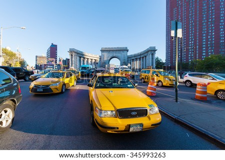 NEW YORK CITY - OCTOBER 11, 2015: Yellow Cabs at the triumphal arch that leads to Manhattan Bridge with unidentified people. The yellow cabs are one of the main iconic symbols of NYC - stock photo