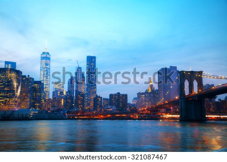 New York City overview with Brooklyn bridge at sunset - stock photo