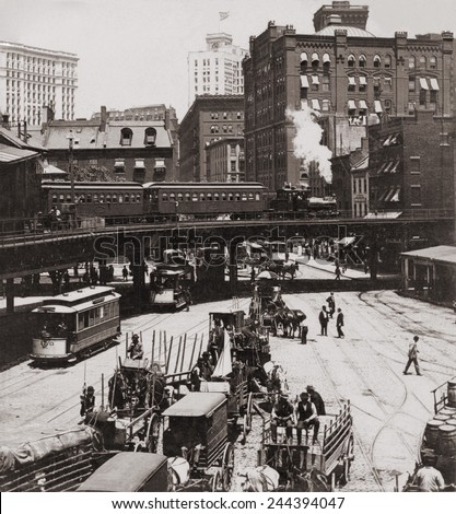 New York City's Elevated Railroad at Manhattan's South Ferry in 1899. The train was pulled by a steam powered engine as trolley cars and horse drawn wagons travel on the street below. - stock photo