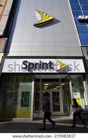 NEW YORK CITY - SEPT. 10, 2014: Pedestrians walk past a Sprint store in New York City, on September 10, 2014. Sprint Corporation is a telecommunications company that provides wireless services. - stock photo