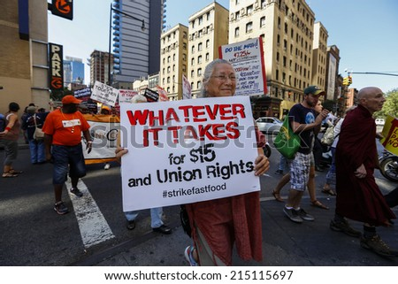 NEW YORK CITY - SEPTEMBER 4 2014: fast food workers & supporters marched along 8th Ave calling for an increase to the minimum wage. Some blocked traffic on 8th Ave leading to several arrests by NYPD - stock photo
