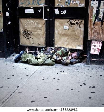 New York City - SEPTEMBER 22: Homeless man asleep on the street on September 22, 2013  in Manhattan, New York. Homelessness effects over 55K people, 21K which are children, each night in NYC. - stock photo
