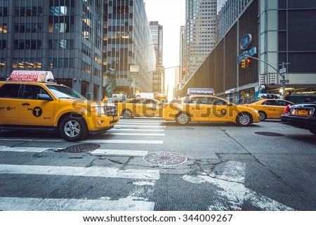New York City - September 15: Manhattan morning sunrise view from 53th yellow cabs at work, passing on 6AV Hilton building, on september 2015. - stock photo