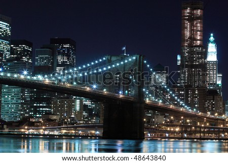 New York City Skyline and Brooklyn Bridge At Night - stock photo