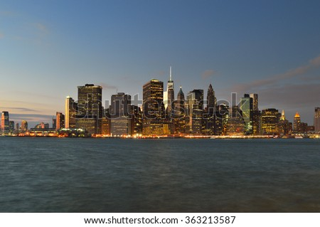 New York City skyline at night with blue sky and illuminated buildings. - stock photo