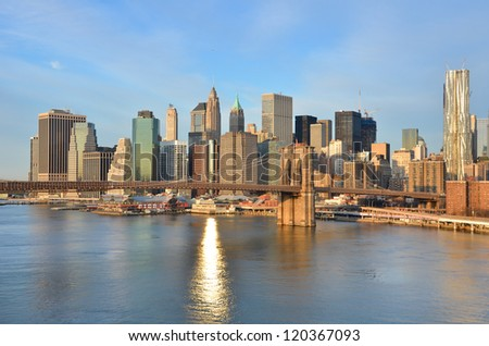 New York City skyline with Brooklyn Bridge and Lower Manhattan view in early morning sun light - stock photo