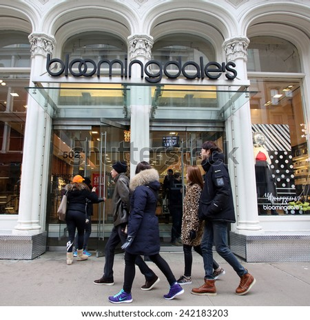 NEW YORK CITY - TUESDAY, DEC. 30, 2014: Pedestrians walk past a Bloomingdale's store. Bloomingdale's is an American upscale chain of department stores owned by Macy's, Inc.  - stock photo