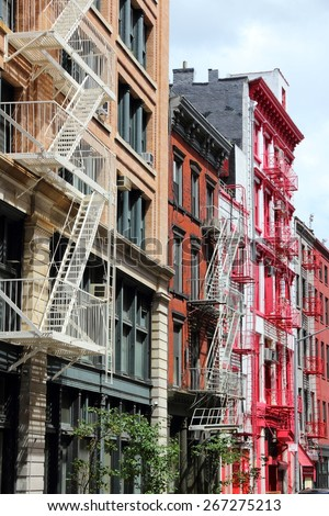 New York City, United States - old residential buildings in Soho district. Colorful fire escape stairs. - stock photo
