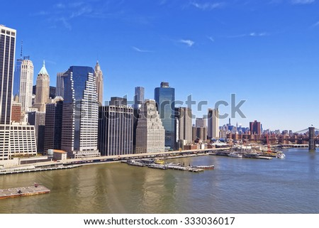 NEW YORK CITY, USA - APRIL 25, 2015: Manhattan downtown panorama over East River with urban skyscrapers and blue sky in New York City, USA on April 25, 2015 - stock photo