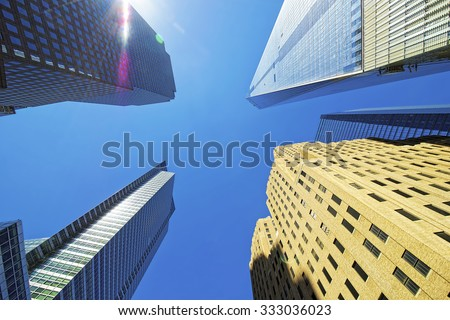 NEW YORK CITY, USA - APRIL 25, 2015: Skyscrapers rising up to sky on Lower Manhattan including the Freedom Tower, New York City, USA. View with picturesque sunlight flares.           - stock photo