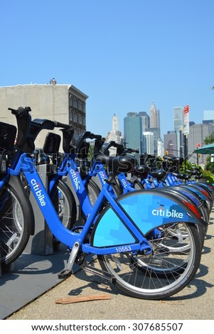 New York City, USA - August 16, 2015: Citi Bikes waiting to be rented in Brooklyn Heights with the Lower Manhattan skyline in the background in New York City. - stock photo