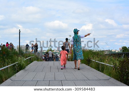 New York City, USA - August 23, 2015: Mother and daughter walking along a path on the High Line on the West Side of Manhattan in New York City. - stock photo