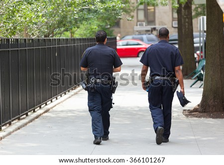 NEW YORK CITY , USA - JULY 07, 2015: Two police officers from the back in the center of Manhattan.. NYPD, established in 1845, is the largest municipal police force in the United States. - stock photo