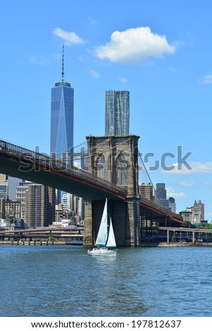NEW YORK CITY, USA - June 6, 2014: Sailboat on the East River passing under the Brooklyn Bridge.  - stock photo