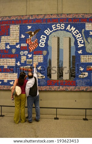 NEW YORK CITY, USA - May 17, 2014: Couple looking at a quilt in the National 9/11 Memorial Museum at Ground Zero in Lower Manhattan.  - stock photo