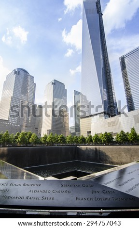 NEW YORK CITY, USA - MAY 30, 2013: Ground level view of the 9/11 memorial which includes one of the two waterfalls and names of the victims in the foreground, and new towers behind. - stock photo