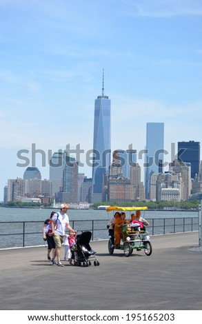 NEW YORK CITY, USA - May 26, 2014: People enjoying Memorial Day on Governors Island in New York Harbor with the Lower Manhattan skyline in the background.  - stock photo