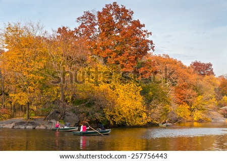 NEW YORK CITY, USA - NOVEMBER 14: People row in recreational boats on a lake in beautiful autumn Central Park, NYC at November 14, 2011. - stock photo