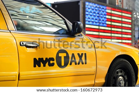 NEW YORK CITY, USA - November 14, 2012:Yellow cab taxi at Times Square in front of the USA national flag. November 14,2012 New York - stock photo