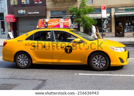 NEW YORK CITY, USA -  31ST AUGUST 2014: A bright yellow New York Taxi moving along a road in Manhattan during the day - stock photo