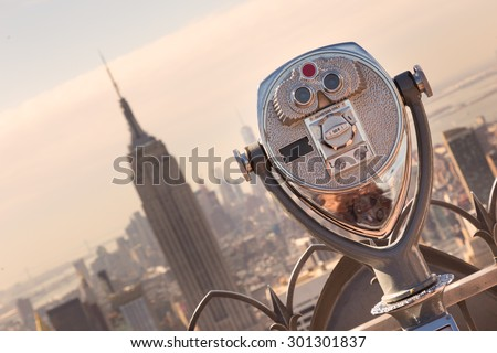 New York City, USA. Vintage tourist binoculars at Top of the Rock observation deck in front of Manhattan downtown skyline with Empire State Building and skyscrapers at sunset.  - stock photo