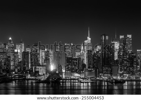 New York City with skyscrapers illuminated over Hudson River panorama in black and white - stock photo