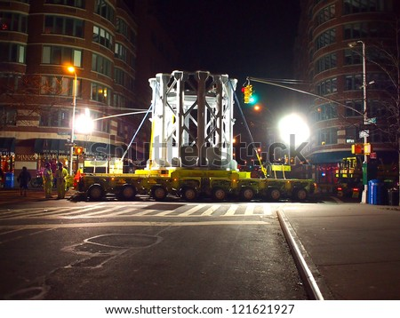 NEW YORK - DEC 12: Workers use a large truck to move a piece of the spire of One World Trade Center early on December 12, 2012 in New York City. The spire was manufactured in sections in Canada. - stock photo