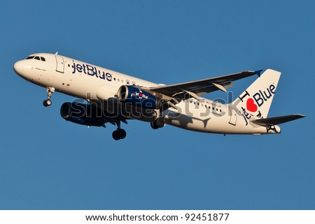 NEW YORK - DECEMBER 21: A320 jetBlue approaching JFK in New York, USA on December 21, 2011. Plane is wearing special livery I love blue York jetBlue as of 2011 is the fastest growing airline in world - stock photo