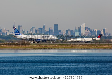 NEW YORK - DECEMBER 8: Airbus A320 JetBlue and Bombardier  jet airliner Delta on JFK in New York USA on December 8, 2012 JFK airport is New York's main international airport opened in 1948 - stock photo