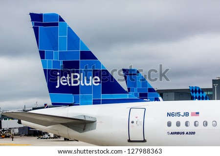 NEW YORK - DECEMBER 9: Airbus A320 JetBlue tailfin Mosaic design on JFK airport in New York, USA on December 9, 2012 JetBlue aircrafts feature one of several tail designs and a name with the word blue - stock photo