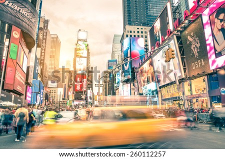 NEW YORK - DECEMBER 22, 2014: blurred yellow taxi cab and rush hour congestion at Times Square in Manhattan, one of the most visited tourist attractions in the world. Warm vintage filtered editing. - stock photo