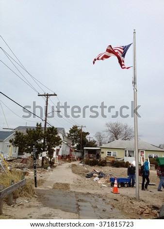 NEW YORK -December 2, 2012: Photo of wreckage and debris from homes destroyed by devastating fire during Hurricane Sandy. American flag flies in background of devastation. - stock photo