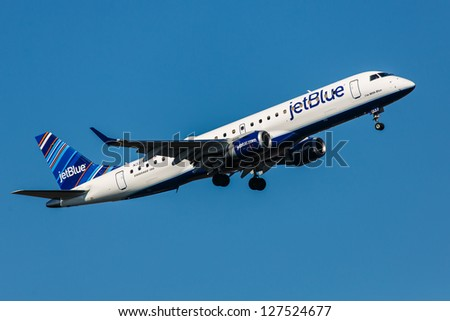 NEW YORK - JANUARY 8: Embraer JetBlue climbs after take off from JFK in New York, USA on January 8, 2013 JetBlue is New York based, fastest growing airline in the world. They use Airbuse and Embraers - stock photo